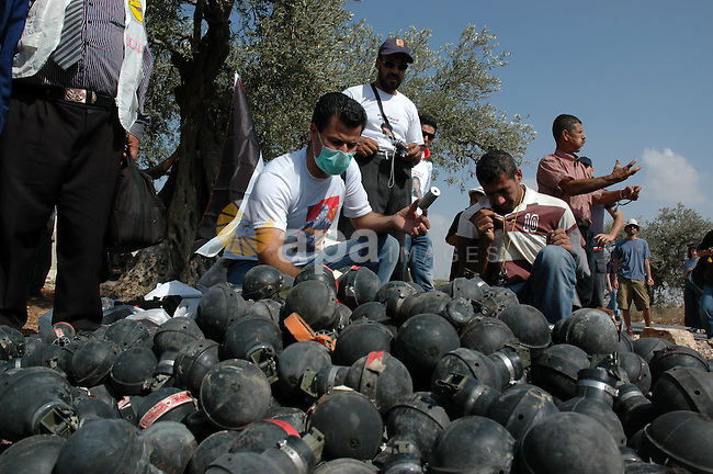 Palestinian and foreign protestors look at a pile of  tear gas canisters fired by Israeli troops during a demonstration against Israel's separation barrier in the West Bank village Bilin near Ramallah on Oct 9, 2009. Photo by Nedal Shtieh