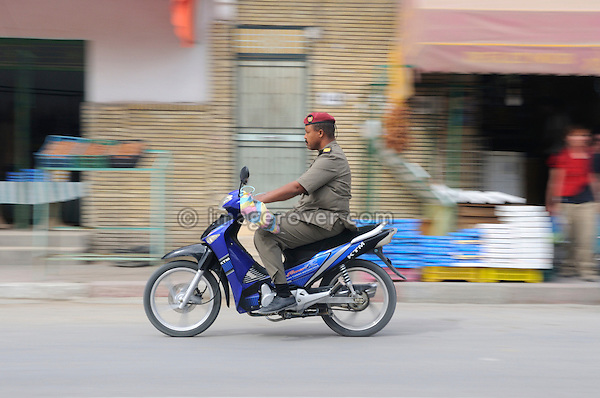 Africa, Tunisia, Tozeur. Tunisian man wearing a uniform on moped. --- No releases available, but releases may not be needed for certain uses. Automotive trademarks are the property of the trademark holder, authorization may be needed for some uses.