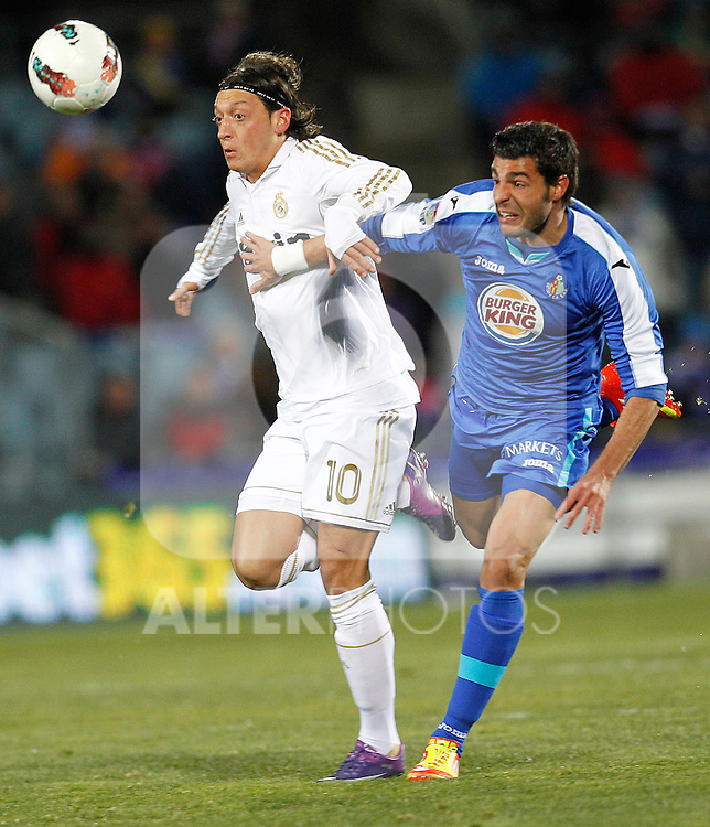 Getafe's Miguel Torres and Real Madrid's Mesut Ozil during la Liga match on February 4th 2012. ..Photo: Cesar Cebolla / ALFAQUI