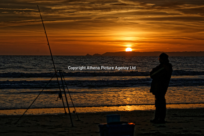 The sun is seen setting over Mumbles Head near Swansea, whie a man is fishing in the nearby beach of Aberavon in south Wales, UK. Wednesday 24 October 2018