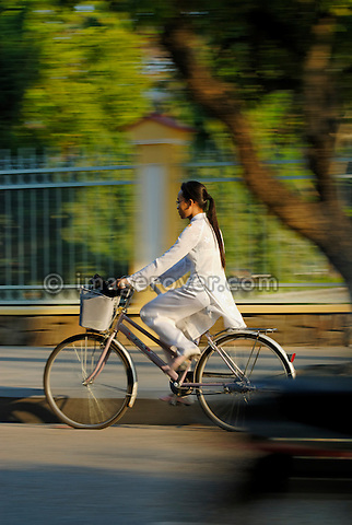 Asia, Vietnam, Hue. Girl in traditional vietnamese white dress returning from school.