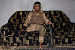 BAGHDAD, IRAQ: Hussein sits on his couch in his army uniform...On January 22nd, 2012, an IED (Improvised Explosive Devise) detonated near an Iraqi Army base in Fallujah. Hussein Jamil Abdullah, a 28 year-old soldier from Baghdad was nearby when the explosive discharged, knocking him to the ground. Hey lay there for half an hour, his right leg in an jerry-rigged tourniquet made from a headscarf, before he was taken to hospital...Gangrene set in almost immediately and the doctors at Fallujah General Hospital had to amputate his leg. He was then moved to Adnan Hospital, the military medical center, but the care Hussein received was terrible. His bandage wasn'.t changed for two days and fearing that gangrene would set in a second time his family moved him to Kerkh Hospital, which they had to cover the costs themselves, as the army refused to pay...As soon as he was wounded, the Army cut Hussein.s salary in half: from $500 a month to $250, which is less than he can live on. His brother, Ali, has given up his work as a barber to take care of him, and his two other brothers, Abbas and Hassan, now take care of the family...Before he was wounded, Hussein, was to be engaged to his fiancée, Hind and he had even bought and furnished a room in preparation. But, after the explosion, Hind.'s father refused to allow them to marry, saying that they can.t do so until Hussein gets a prosthetic leg...In the summer, a selection of photographs were published online and caught the attention of an NGO worker in Baghdad who arranged for Hussein to have a prosthetic leg fitted...Once he had his prosthetic leg, Hussein married Hind...Photo by Ali Arkady/Metrography
