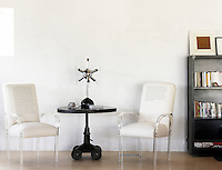 A pair of acrylic armchairs each sporting a quotation flanks a pedestal table with a 1960s style lamp
