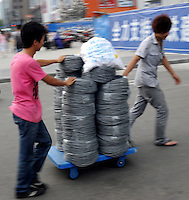 Two cable service workers walk pass with meters of internet cable, Chengdu, China. According to latest report, China's broadband subscribers will rise to 183.9 million by 2014, up from 103.2 million in 2009...