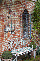 A wrought-iron garden bench is situated against the mellow brick wall next to one of the arabesque shaped windows with a candle lantern suspended from the vine above
