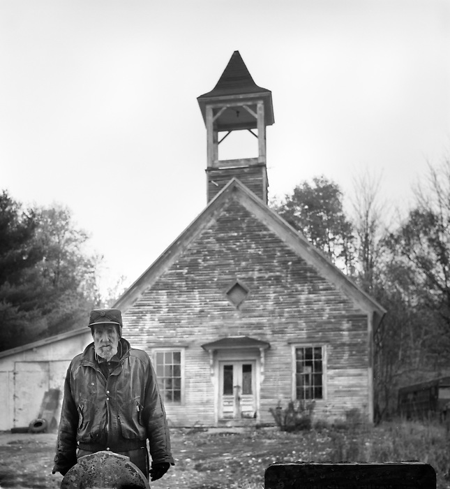 An old man standing in front of a Grave with an old church in the background