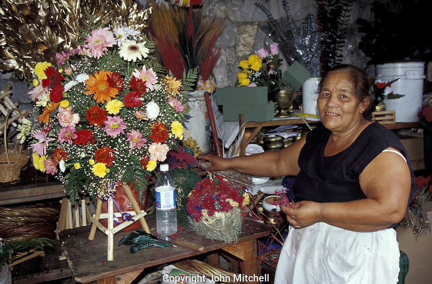 Woman standing next to flower arrangement in the Guamilito Market, San Pedro Sula, Honduras