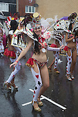 London, UK. 25 August 2014. Performers from the Paraiso School of Samba. Visitors and participants of the Notting Hill Carnival 2014 Bank Holiday Monday parade got soaked to their skin, but the weather couldn't dampen the revellers spirit - although many spectators stayed away.