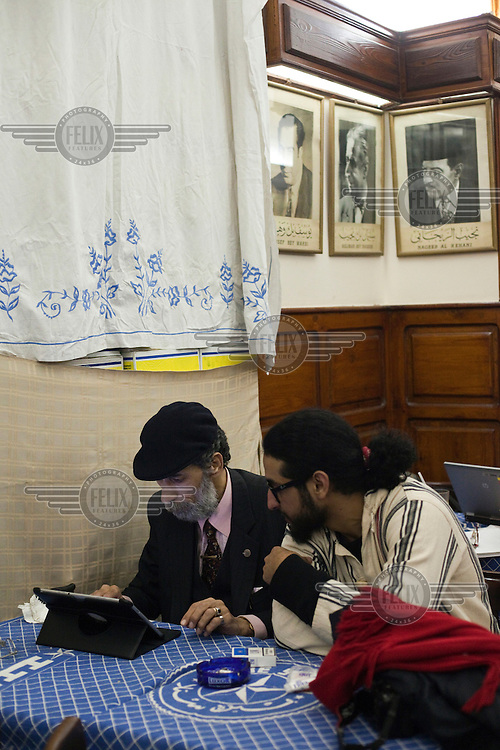Celebrated political cartoonist Hassaneen Bassen (left) and Murad, his young protege, sit at a table in Cafe Riche looking at a tablet computer together. /Felix Features