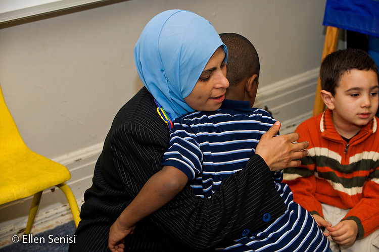 MR / Jersey City, NJ.Al-Ghazaly Elementary School (private Islamic school with a curriculum that follows state curriculum content standards and also teaches Islamic studies) / Pre-K classroom.Teacher (Egyptian-American, wearing hajib) hugs student (boy; 4; African-American)..ID: AI_gPag  MR: Hal4 Kni1 Moh1.© Ellen B. Senisi