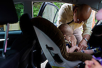 Fred Bermont puts son Dylan Bermont (age 9 months) in a car seat as he drops the kids off at day-care in Lexington, Massachusetts, USA, before he goes to work on June 9, 2014. Bermont is the father of two children and shares parenting duties with his wife, Jen Bermont. Fred usually takes care of the morning routine, including feeding, dressing, and dropping the kids off at day-care, and Jen picks them up and watches over them in the afternoon. Fred is a Senior Clinical Standards Specialist at Shire, a pharmaceutical company with headquarters in Lexington.