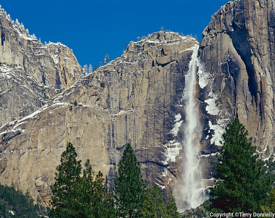 Yosemite National Park, CA: A dusting of snow on granite cliffs and the Upper Yosemite Fall under blue skies