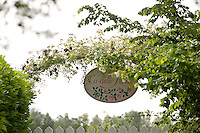 Detail of the sign hanging under a rose arch at the entrance of the Ca' delle Rose garden in Italy