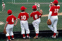 Four Young Little League Baseball Players in Red and White Team Uniforms watching Game of Softball / Hardball at Ball Park