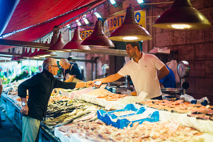 Sicilian person buying seafood at Ortigia Market, Syracuse (Siracusa), Sicily, Italy, Europe. This is a photo of a Sicilian person buying seafood at Ortigia Market, Syracuse (Siracusa), Sicily, Italy, Europe.