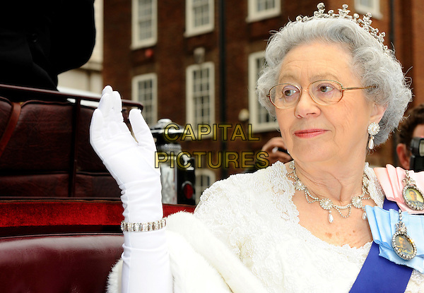 QUEEN ELIZABETH II LOOKALIKE.At the launch of her new book 'Kate And Wills Up The Aisle' at Waterstones, Piccadilly, London, England, UK,.April 1st, 2011..photocall impersonator look-a-like royal half length red April fool's day blue sash white glasses glove tiara fur  necklace earrings pearls  sitting in carriage hand waving .CAP/CJ.©Chris Joseph/Capital Pictures.
