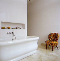 A patterned chair strikes a colourful note on the pale marble floor of this contemporary bathroom