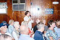 A woman asks a question of Republican presidential candidate and Ohio governor John Kasich at a town hall campaign event at the Derry VFW in Derry, New Hampshire.