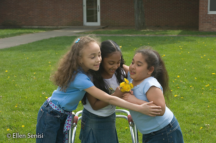 MR / Schenectady, NY.Zoller school (urban public school) / grade 2 Inclusion class.Friends look at flowers and dandelions together on playground. (Girl with walker: 7, cerebral palsy; girl with light blue shirt and denim skirt: 8, African-American / Puerto-Rican / Caucasian, Congenital Heart Disease, Hip Dysplasia; other girl: 8).MR: Goo9, Cha9, Gar6.© Ellen B. Senisi