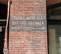 A sign on the wall of building in the New York neighborhood of Soho warns truck drivers of a vault underneath the sidewalk,  on Sunday, June 7, 2015. Many buildings have basements that extend underneath the sidewalk, called a vault. The hollow space cannot support the weight of a vehicle. New York started to tax vaults in 1962 but enforcement began in earnest in 1989. Many owners sealed off the vault to avoid the tax but the hollow space remains. (© Richard B. Levine)