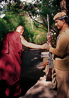 The Dalai Lama blessing his guard holding a rifle   <br /> Dharamsala, India 1998<br /> I first met His Holiness the Dalai Lama in 1988 and have had the great fortune to photograph him a number of times over the years. I've always enjoyed our conversations but sometimes it's his gestures that hold the most meaning. One day we were walking through the lovely bamboo shaded lane from his home to his office as we passed one of his ever-present guards. Suddenly the Dalai Lama stopped. Placing one hand on the soldier's hand holding the rifle, he chanted a prayer and moved on. I quickly lifted my camera and managed to take one frame. The guard simply beamed.
