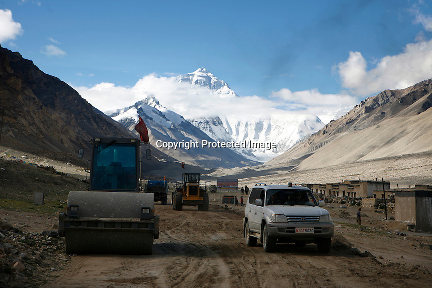 China started building a controversial 67-mile &quot;paved highway fenced with undulating guardrails&quot; to Mount Qomolangma, known in the west as Mount Everest, to help facilitate next year's Olympic Games torch relay./// A digger rolls past Rongbuk Monastery  on the road to Everest Base Camp.<br /> Tibet, China<br /> July, 2007