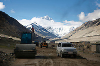 "China started building a controversial 67-mile ""paved highway fenced with undulating guardrails"" to Mount Qomolangma, known in the west as Mount Everest, to help facilitate next year's Olympic Games torch relay./// A digger rolls past Rongbuk Monastery  on the road to Everest Base Camp.<br /> Tibet, China<br /> July, 2007"