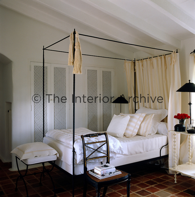 One of a pair of single metal-framed four-poster beds in a guest bedroom