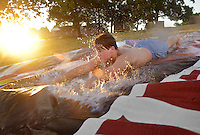 NWA Democrat-Gazette/BEN GOFF &bull; @NWABENGOFF<br /> Justin Kem, 15, takes a ride down a roughly 150 yard waterslide on Saturday Aug. 1, 2015 at the home of Hutch Kufahl in Bentonville. Kufahl, youth pastor at First Baptist Church of Bentonville, organized the waterside as an activity for his Studio 412 high school youth group.