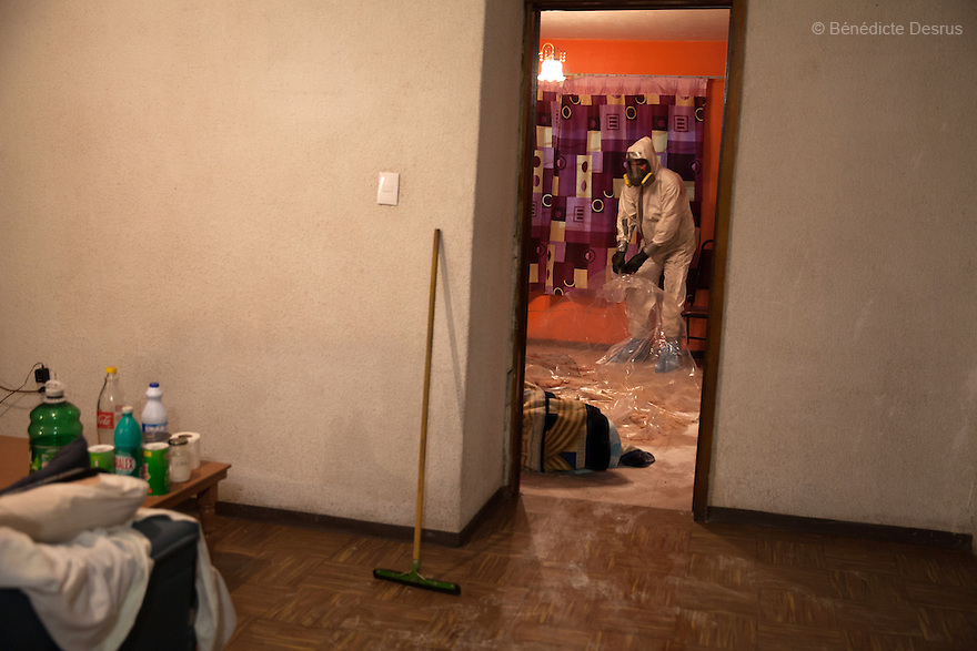 "Donovan carries out a forensic cleaning in Iztacalco, Mexico on October 16, 2015. The decomposed body of a man in his 60s was found in his bedroom a number of days after he died of a heart attack – although the deceased's own family members were unsure exactly how long he had been there. The victim's family remarked that the police had made unfounded insinuations against them, and had sought bribes. As a result they found Donovan's discretion and professionalism to be a welcome contrast. Donovan Tavera, 43, is the director of ""Limpieza Forense México"", the country's first and so far the only government-accredited forensic cleaning company. Since 2000, Tavera, a self-taught forensic technician, and his family have offered services to clean up homicides, unattended death, suicides, the homes of compulsive hoarders and houses destroyed by fire or flooding. Despite rising violence that has left 70,000 people dead and 23,000 disappeared since 2006, Mexico has only one certified forensic cleaner. As a consequence, the biological hazards associated with crime scenes are going unchecked all around the country. Photo by Bénédicte Desrus"