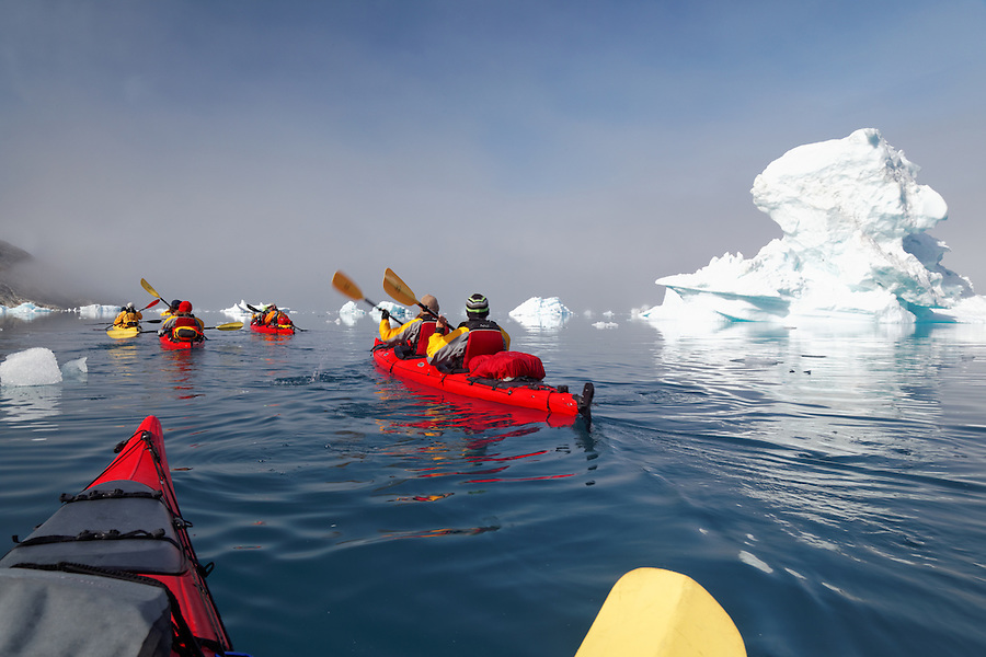 Sea kayakers paddling among icebergs on Sermilik Fjord near settlement of Tiniteqilaq, East Greenland