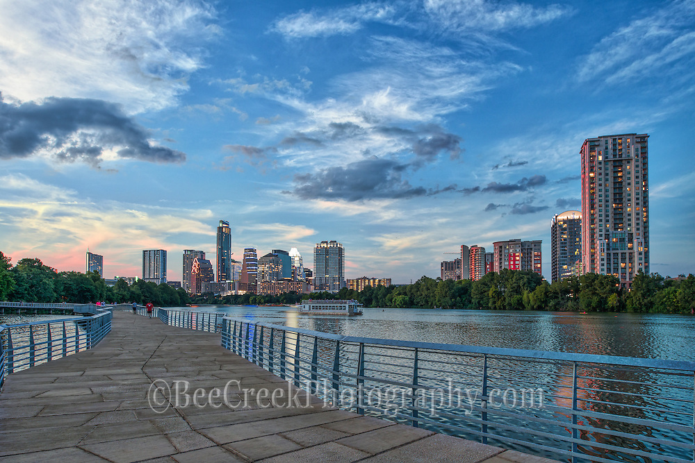 "This is an image of the Austin boardwalk at dusk with one of the toursit boats on Ladybird Lake taking in the sunset. Austin is home to the State Capital with a beautiful skyline along Ladybird Lake.  There are many new high rises buildings in the downtown area of the city which can be seen from the boardwalk hike and bike trail as seen in this photo.  Austin Texas is the capital of Texas and the city is growing at leaps and bounds many of these downtown high rises skyscrapers were not here ten years ago most have gone up in the last five years. In this photo we capture beautiful fall colors on  this December day with the tree displaying colors from the hike and bike trail with one of the paddle boat on the water full of tourist enjoying a nice day on Ladybird Lake and a lovely city view. The skyline of Austin is always changing and the downtown area has many new residences who live in the city so it is a very active place with many restaurants, several parks, hike and bike trails, the warehouse district night life and of course six street where the term ""Live Music Capital"" came from. Sometimes living in Austin for locals can be difficult, because there is always something going on so a lazy walk down the trails may turn in to a fight for a parking space, but for those that live in the city it just a heart beat away."