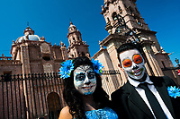 A young couple, costumed as 'La Catrina', a Mexican pop culture icon representing the Death, poses for a picture during the Day of the Dead festivities in Morelia, Michoacán, Mexico, 1 November 2014. Day of the Dead ('Día de Muertos') is a syncretic religious holiday, celebrated throughout Mexico, combining the death veneration rituals of the ancient Aztec culture with the Catholic practice. Based on the belief that the souls of the departed may come back to this world on that day, people gather on the gravesites praying, drinking and playing music, to joyfully remember friends or family members who have died and to support their souls on the spiritual journey.