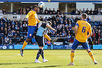 Krystian Pearce of Mansfield Town (left) beats Paul Hayes of Wycombe Wanderers (2nd left) in an aerial battle while Lee Collins of Mansfield Town (right) looks on during the Sky Bet League 2 match between Wycombe Wanderers and Mansfield Town at Adams Park, High Wycombe, England on 25 March 2016. Photo by David Horn.
