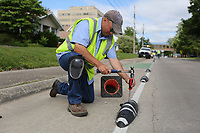 Chris Beck, with signs and markings with the city of Springdale Public Works, removes a Zebra bike lane delineator Tuesday, May 19, 2020, on Maple Avenue in Springdale. The Zebras will remain in the area near Northwest Medical Center and LISA Academy but be removed from other streets. The removed Zebras will be replaced with a raised pavement marker. Check out nwaonline.com/200519Daily/ and nwadg.com/photos for a photo gallery.<br /> (NWA Democrat-Gazette/David Gottschalk)