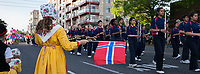 Little girl wearing traditional Norwegian yellow dress waving Norway Flag, 17th of May Parade 2016, Ballard, Seattle, WA, USA.