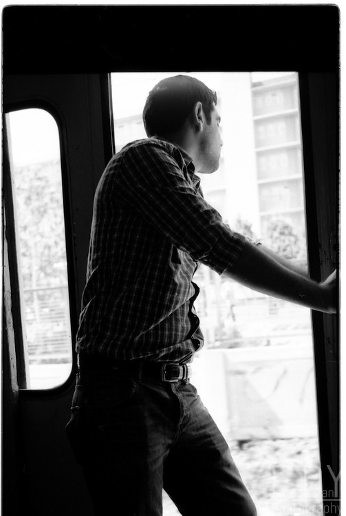 Man looking outside the open door while taking a ride on a suburban train on the european side of Istanbul.