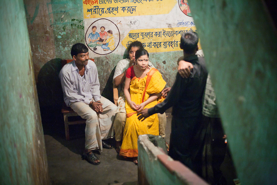 """Faridpur Brothel is the second to largest brothel in Bangladesh. (17 registered brothels in the country) 600+ girls live in a hidden neighboorhood accesible through one of the six alleyways, covered with small ragged curtains mimicking doors. Many girls are under aged - the """"legal"""" age being 18. The chhukris wait during long periods of time for clients to walk past their rooms, the girls are forced to stake out their territory 24h/7 365 days a year. March 16, 2011. Gabriela Barnuevo."""