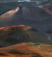 Male and female hiker minimized by the massive cinder cones in the crater of HALEAKALA NATIONAL PARK on Maui in Hawaii