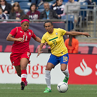 Brazilian player Marta (10) dribbles as Canadian midfielder Desiree Scott (11) defends. In an international friendly, Canada defeated Brasil, 2-1, at Gillette Stadium on March 24, 2012.