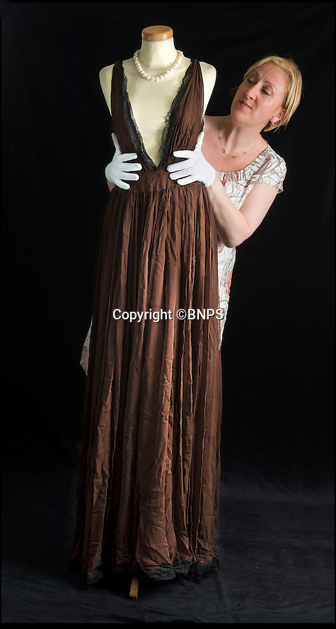 BNPS.co.uk (01202 558833)<br /> Pic: PhilYeomans/BNPS<br /> <br /> Haute couture expert at Dukes Antoinette Rogers with the silk negligee worn by Loren when attempting to seduce Sellers in the movie.<br /> <br /> Dressed to thrill - the stunning dress that led to Peter Sellers infatuation with screen goddess Sophia Loren is coming up for auction - but you may have to actually be a Miliionairess to afford it.<br /> <br /> Sophia Loren stripped off the salmon pink Balmain gown in a racy scene from the 1960 blockbuster 'The Millionairess' and unlikely leading man Peter Sellers was so entranced by the beautiful young italian star that he offered to leave his new wife for her.<br /> <br /> Dukes auctioneers in Dorchester are now selling the dress along with two others from the film and haute couture expert Antoinette Rogers says it could go for up to £10,000 thanks to its unique and glamorous provenance.