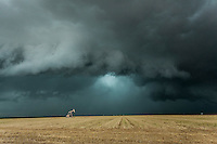 Green supercell thunderstorm above an oil pump in a golden grassy field in Texas, May 26, 2014