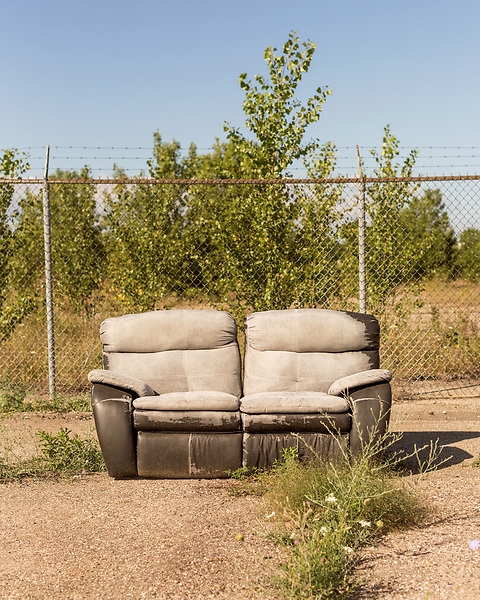 August 6, 2016. Flint, Michigan.<br />  A couch is left on the street near a bridge over the Flint River. <br />  In April 2014, the city of Flint switched its water source from the Detroit Water and Sewerage Department to using the Flint River in an effort to save money. When the switch occurred, the city failed to have corrosion control treatment in place for the new water. This brought about a leaching of lead from pipes into the water, increasing the lead content in the drinking water to levels far above legal limits. After independent sources brought this to light, the city admitted the water was unsafe and legal battles have ensued between resident and the local and state governments.