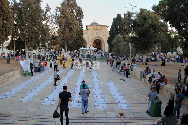 Palestinian muslims prepare to break their fast during the holy fasting month of Ramadan in front of the Dome of the Rock mosque at the al-Aqsa mosque compound, in Jerusalem's old city on June 21, 2016. Ramadan is sacred to Muslims because it is during that month that tradition says the Koran was revealed to the Prophet Mohammed. The fast is one of the five main religious obligations under Islam. More than 1.5 billion Muslims around the world will mark the month, during which believers abstain from eating, drinking, smoking and having sex from dawn until sunset. Photo by Mahfouz Abu Turk