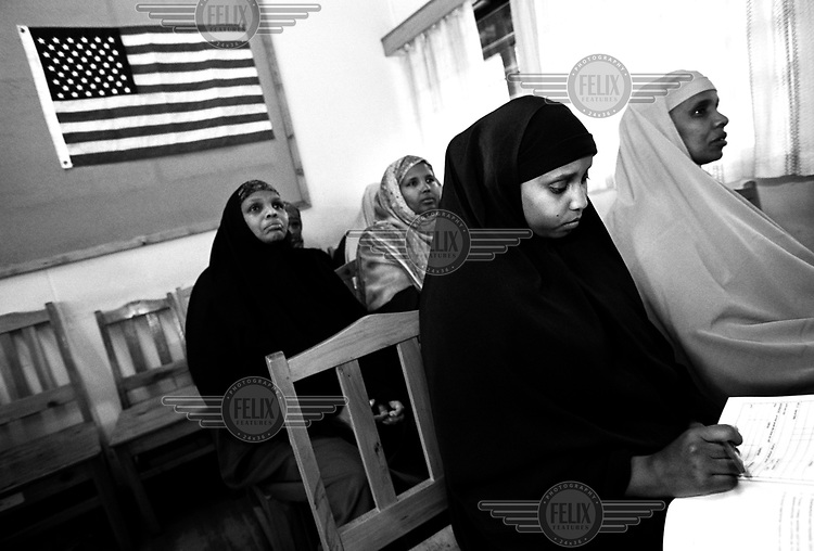 ©Sven Torfinn/Panos Pictures..Kenya, Nairobi, June 2002.Somali people in class at IOM (International Organisation for Migration) in Nairobi, where they receive information about life in the United States of America, their destination in the framework of AmericaÕs resettlement-program for refugees..Somali women are listening to teacher, during classes, in traditional dresses, background American flag.