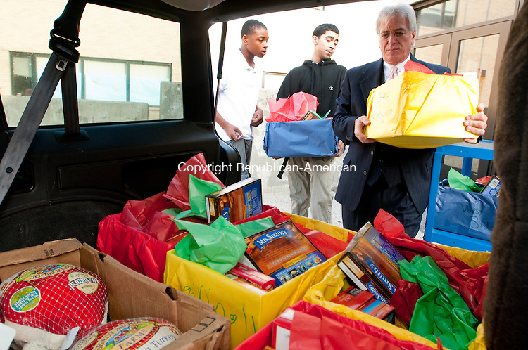 WATERBURY, CT, 23 NOVEMBER 2010-112310JS05--Charles Nappi, right, principal at West Side Middle School, with the help of eight grade students Juwan Butler and Gino Galazo, load turkeys and Thanksgiving dinner packages for delivery to local needy families Tuesday at the school in Waterbury. <br />  Jim Shannon Republican-American