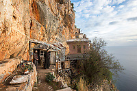 Mount Athos - The Holy Mountain.<br /> Monks look out from their cell which clings to the cliffs of Karoulia.