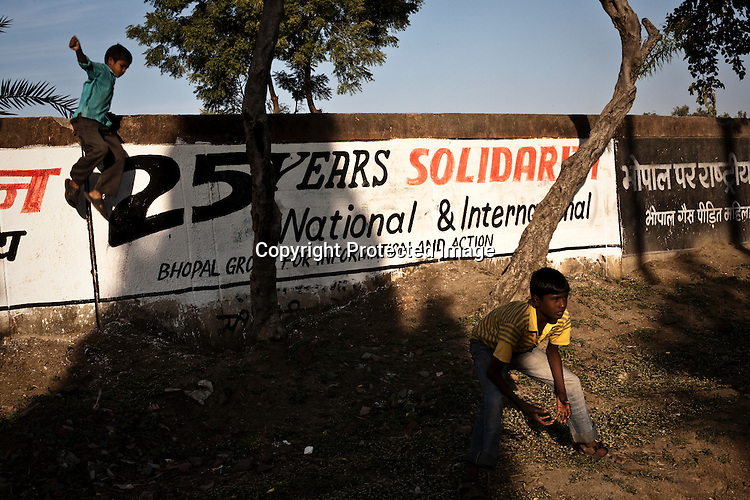 Young boys are seen playing cricket around the perimeter wall at the site of the Union Carbide factory in Bhopal, India. Twenty-five years after an explosion causing a mass gas leak, in the Union Carbide factory in Bhopal, killed at least eight thousand people, toxic material from the 'biggest industrial disaster in history' continues to affect local Bhopalis. A new generation is growing up sick, disabled and struggling for justice. The effects of the disaster on the health of generations to come, both through genetics, transferred from gas victims to their children and through the ongoing severe contamination, caused by the Union Carbide factory, has only started to develop visible forms recently. Photograph: Sanjit Das