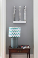 Three antique statues hover on a shelf above a cheerful blue and white striped table lampshade
