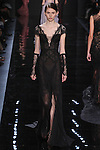 """Model walks runway in a black lace dress with chiffon overskirt from the Reem Acra Fall 2016 """"The Secret World of The Femme Fatale"""" collection, at NYFW: The Shows Fall 2016, during New York Fashion Week Fall 2016."""